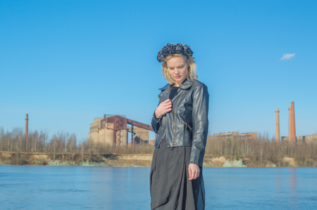 a girl in a black wreath on the background of the old plant. Imagens