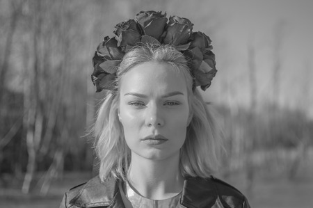 black and white, girl with a wreath of black flowers, closeup.