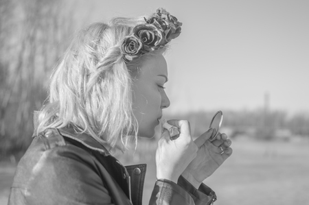 black and white, a girl in a black wreath putting on makeup. Imagens