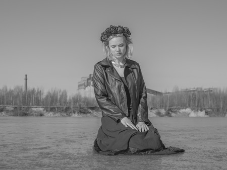 black and white, a girl in a black wreath sits on the ice.