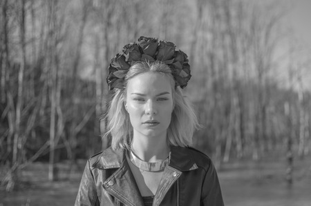 black and white, portrait of girl with wreath of black flowers on his head. Imagens