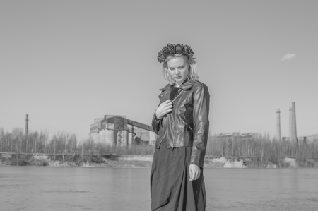 black and white, a girl in a black wreath on the background of the old plant.