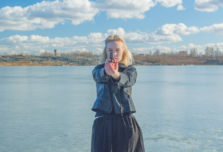 quite: girl aiming a pistol at the background of the lake.
