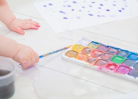 La mano del bebé con pincel y pinturas. Foto de archivo - 77984059
