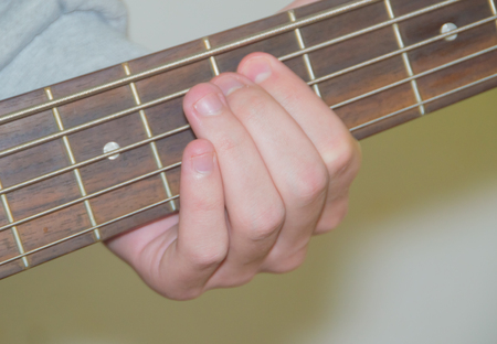 the hand on the fingerboard and the strings of the guitar.