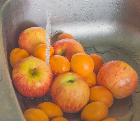 fruit, apples and peaches under the water flow.