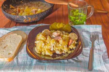 op de handdoek is een gerecht van gebakken aardappelen in eieren met worstjes en kruidenthee.
