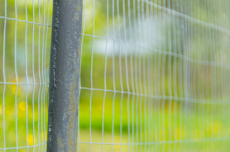 closeup of a fence made of metal pipes and steel mesh fencing. Stok Fotoğraf