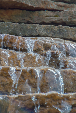 background, water running through the stratified rocks.