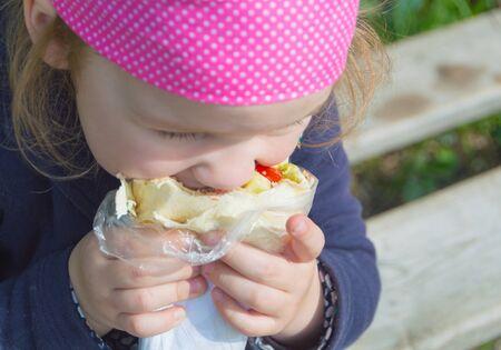 close-up on the street eats fast food kid.
