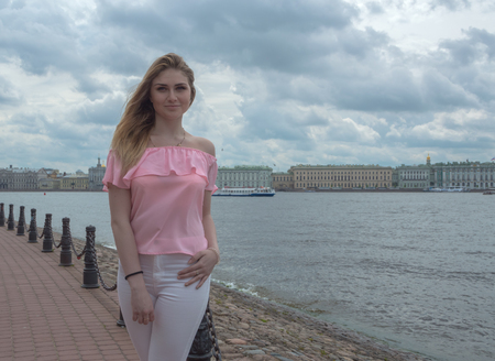 川の近くのピンクのブラウスで美しい少女。 写真素材