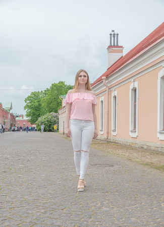 on the pavement an attractive girl in a pink blouse.
