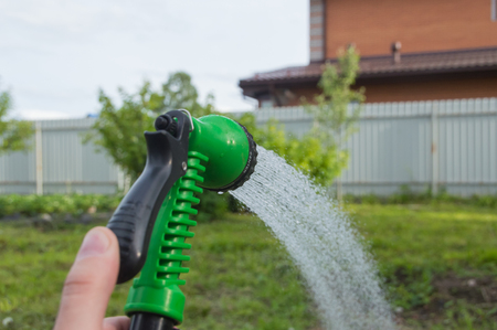 with garden watering hose watering the lawn.