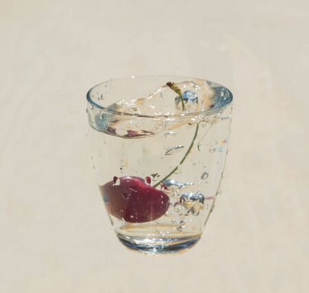 in a transparent glass with water splashes cherry. Banco de Imagens