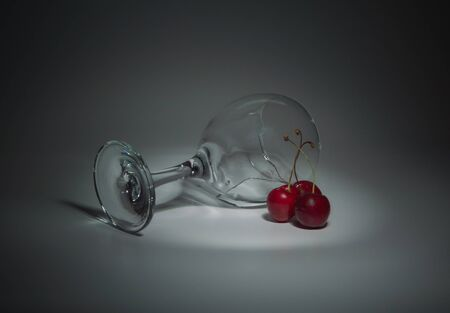 intoxicate: closeup on a white background lies a glass with cherries and water.