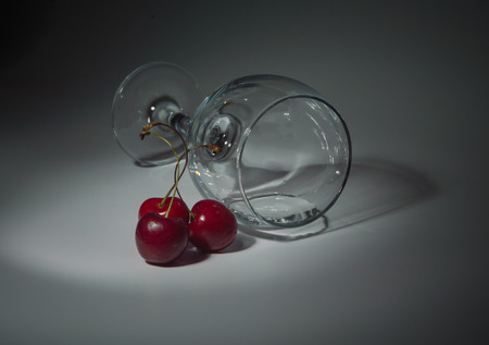intoxicate: closeup, white background glass with cherries and water.