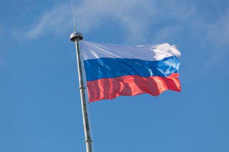op de vlaggenmast ontwikkelt in de wind de vlag van Rusland.