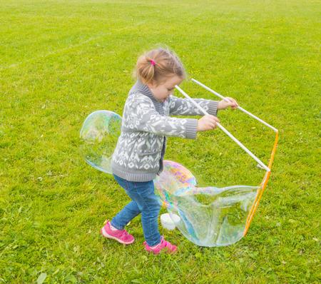 baby meisje met dergelijke grote zeepbellen op straat.