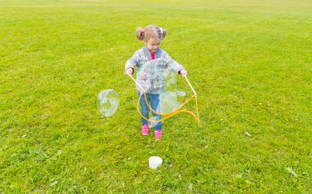 Baby meisje met zo'n grote ronde bubbels op de straat.