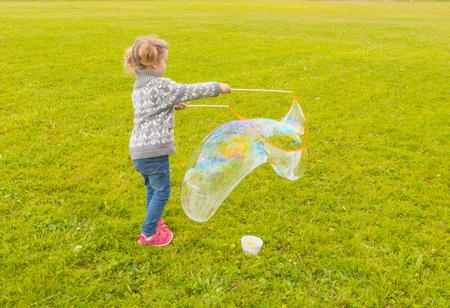 baby meisje met dergelijke grote zeepbellen in het park.