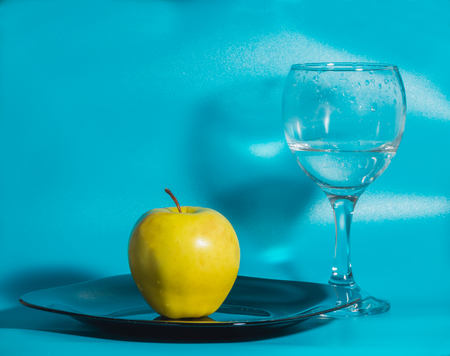 yellow Apple in the plate with a glass of water on a blue background. Stock Photo