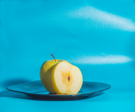 yellow Apple in the plate on a blue background.