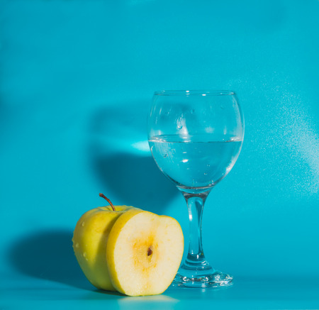yellow Apple with a glass of water on a blue background.