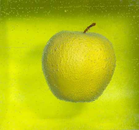 yellow Apple in the air bubbles on a green background.