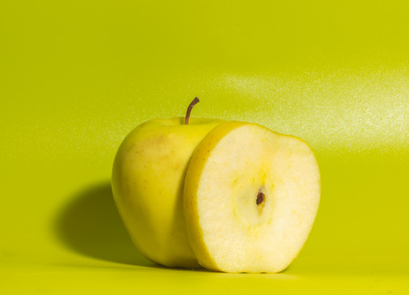 closeup, yellow Apple on a green background. Stock Photo