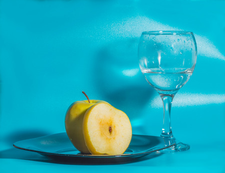 on a blue background yellow Apple in the plate with a glass of water. Stock Photo