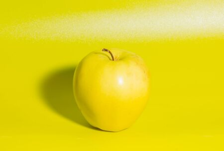 closeup on green background yellow Apple.