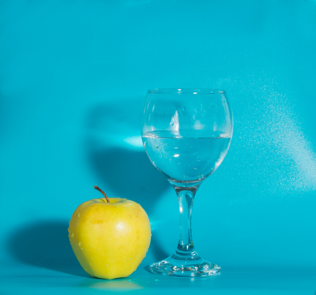 on a blue background yellow Apple with a glass of water.