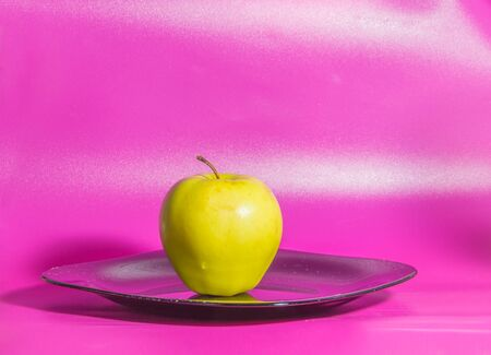 the plate a yellow Apple on a pink background.