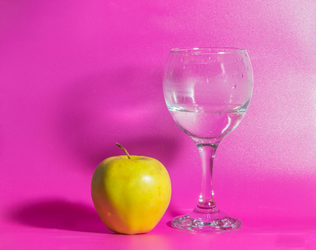 yellow Apple with a glass of water on a pink background. Stock Photo
