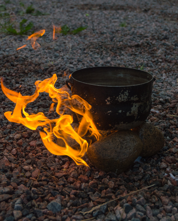 the burn with a bright flame stones and camp pot. Stock Photo