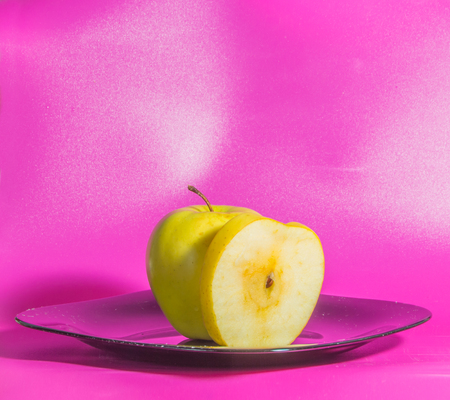 on a pink background on the plate yellow Apple. Stock Photo