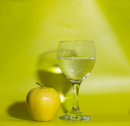 on a green background yellow apples with a glass of water. Stock Photo