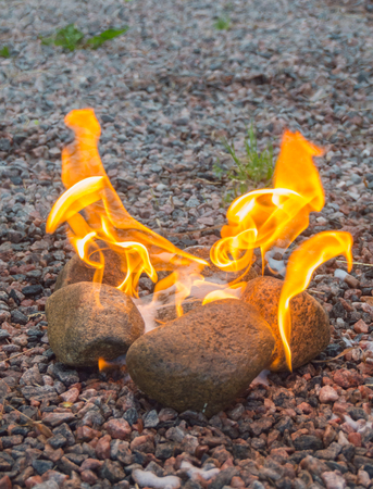 outdoor fireplace: a the stones are burning bright with fire.