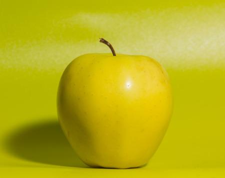yellow Apple on green background, closeup.