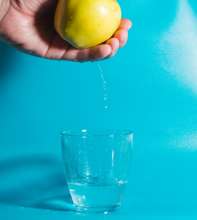 yellow Apple in his hand, and falling water drops into the glass.