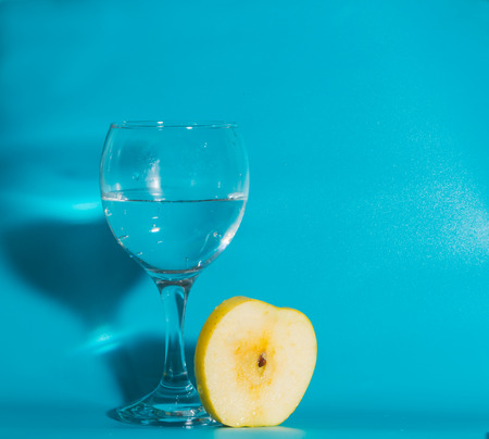 slice of yellow Apple with a glass of water on a blue background. Stock Photo