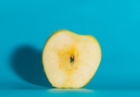closeup, slice of yellow Apple on a blue background. Stock Photo