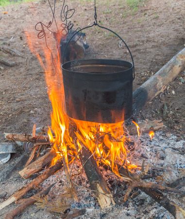 in the campaign pot of water over the fire. Stock fotó
