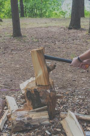 彼の手で薪を分割するための斧。