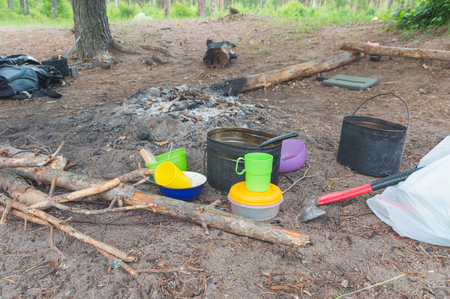 near the camp fire utensils for food.