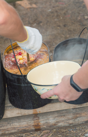 applied food with a ladle from the pot in the campaign. Stock fotó