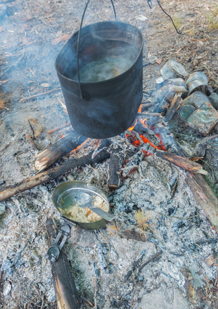 Breakfast in nature, cereal in a bowl, heated on a fire.