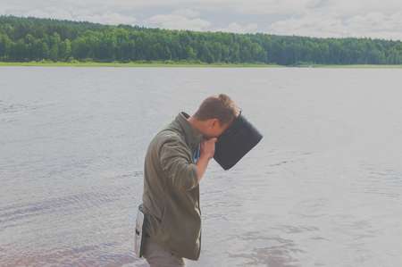 a man looks in a pot on a background of lake and forest.