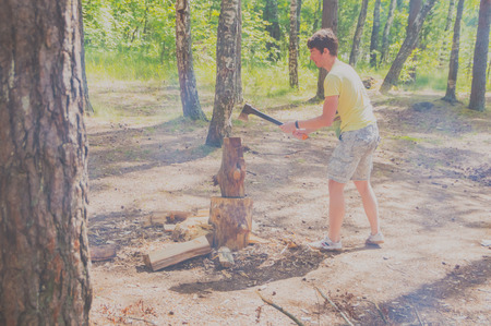 July 15, 2017 Russia, the Vuoksi river, Losevo - in the forest with an ax chopping wood man.