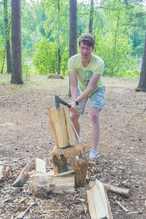 July 15, 2017 Russia, the Vuoksi river, Losevo - a man chops wood with an ax in the woods.